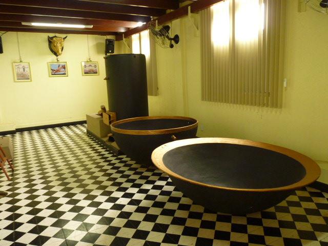 Sala de exposição: no alto, uma cabeça de boi em meta caldeira com dois tachos para escaldamento de vísceras de animais; pedra de abate de animais; argola para prender boi.